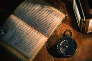 opened book beside compass