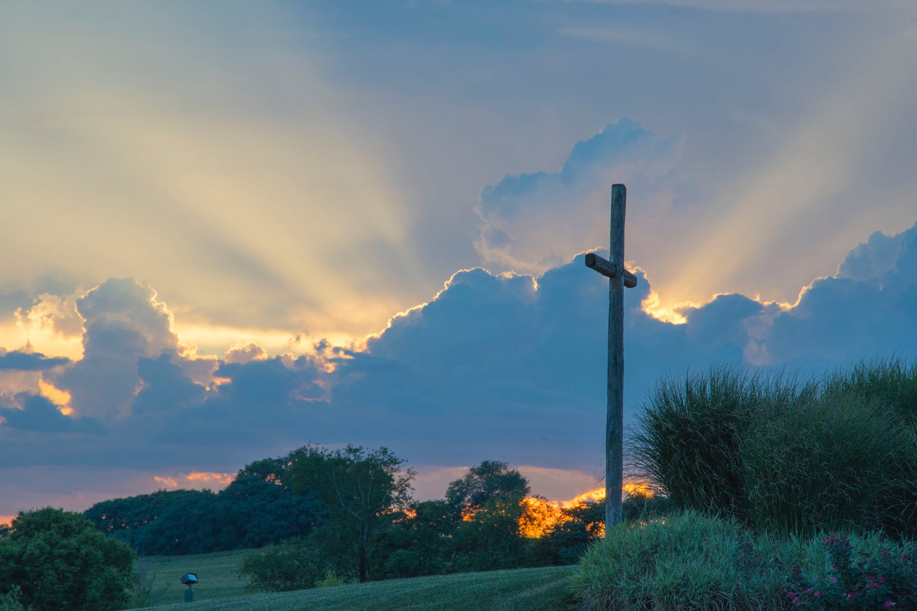 big wooden cross on green grass field under the white clouds