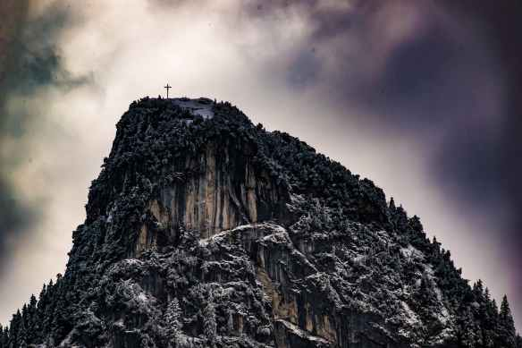 low angle photography of cross on top of mountain