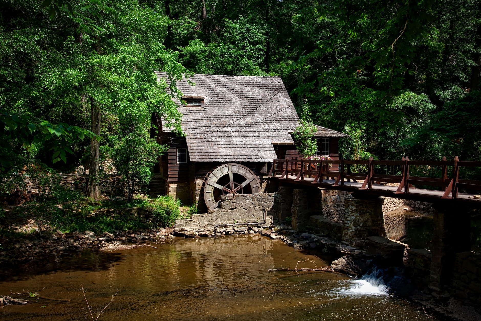 brown house near river trees and bridge