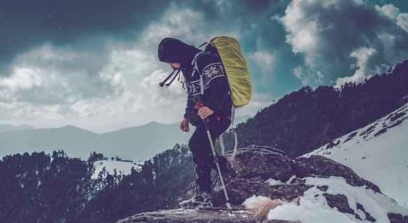 man wearing black hoodie on rock edge