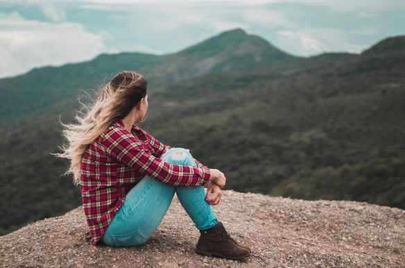 side view photo of woman sitting on ground overlooking a hill