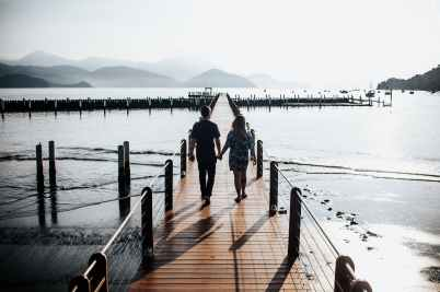 back view photo of couple holding hands while walking down wooden dock