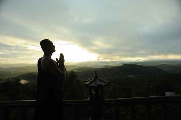 monk holding prayer beads across mountain