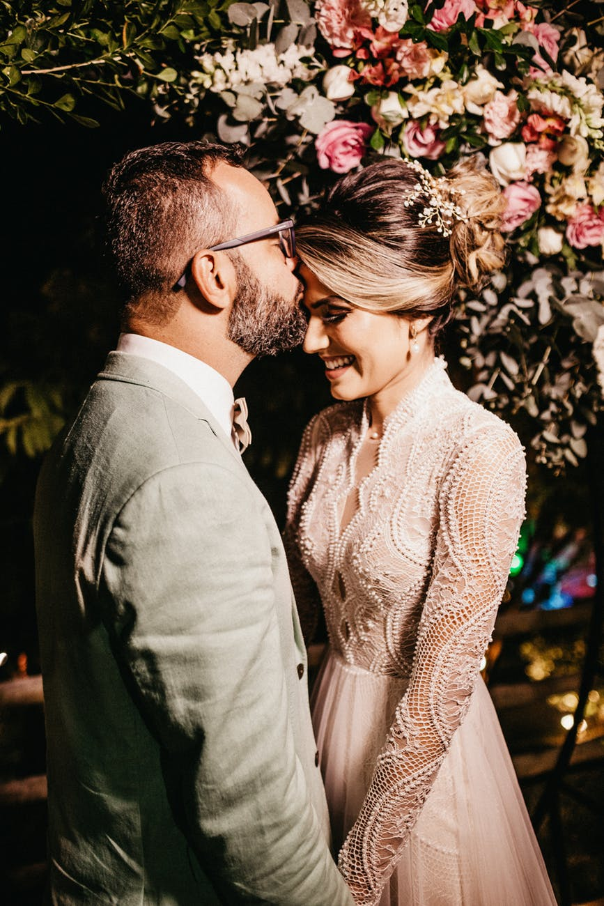 man kissing woman forehead