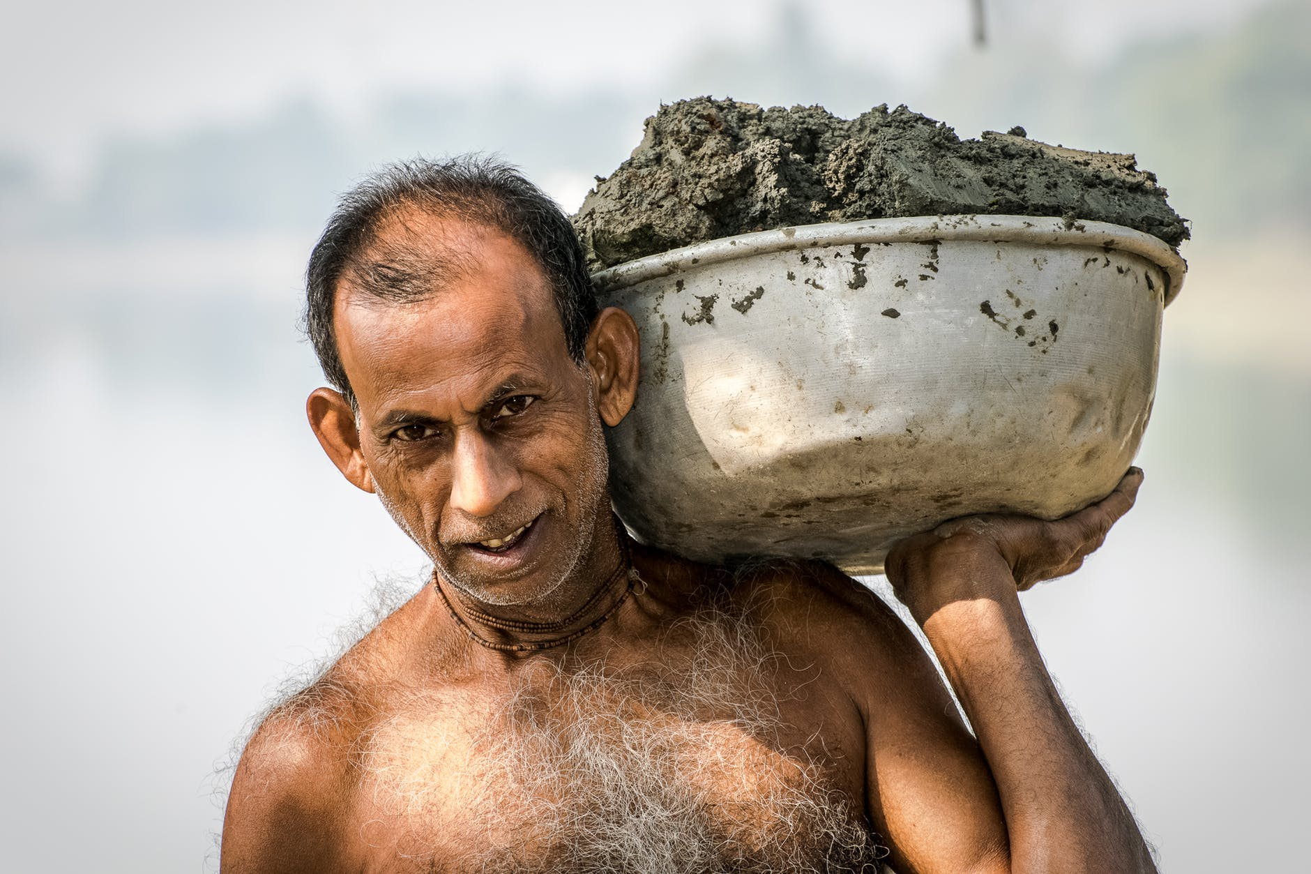 man carrying bucket of mud