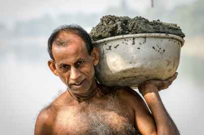 man carrying bucket of mud