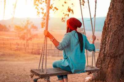 woman sitting on swing beside tree