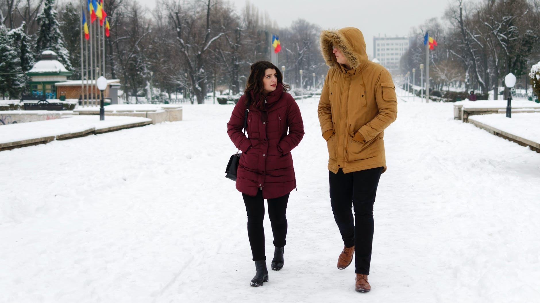 man in brown parka jacket walking beside woman in maroon coat