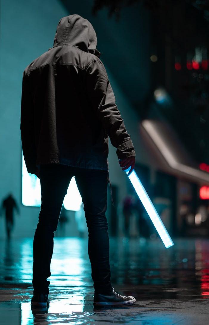 man wearing black hoodie standing on concrete pavement at night