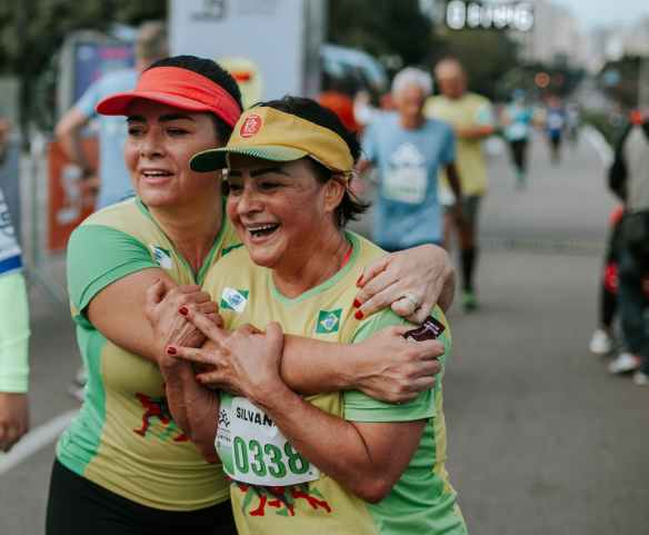 two smiling women wearing yellow and green shirts