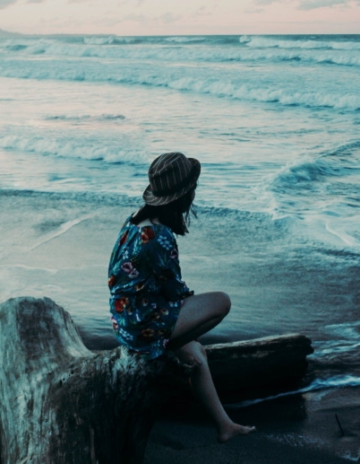 photo of woman in floral dress sitting alone on a log by the beach overlooking the horizon