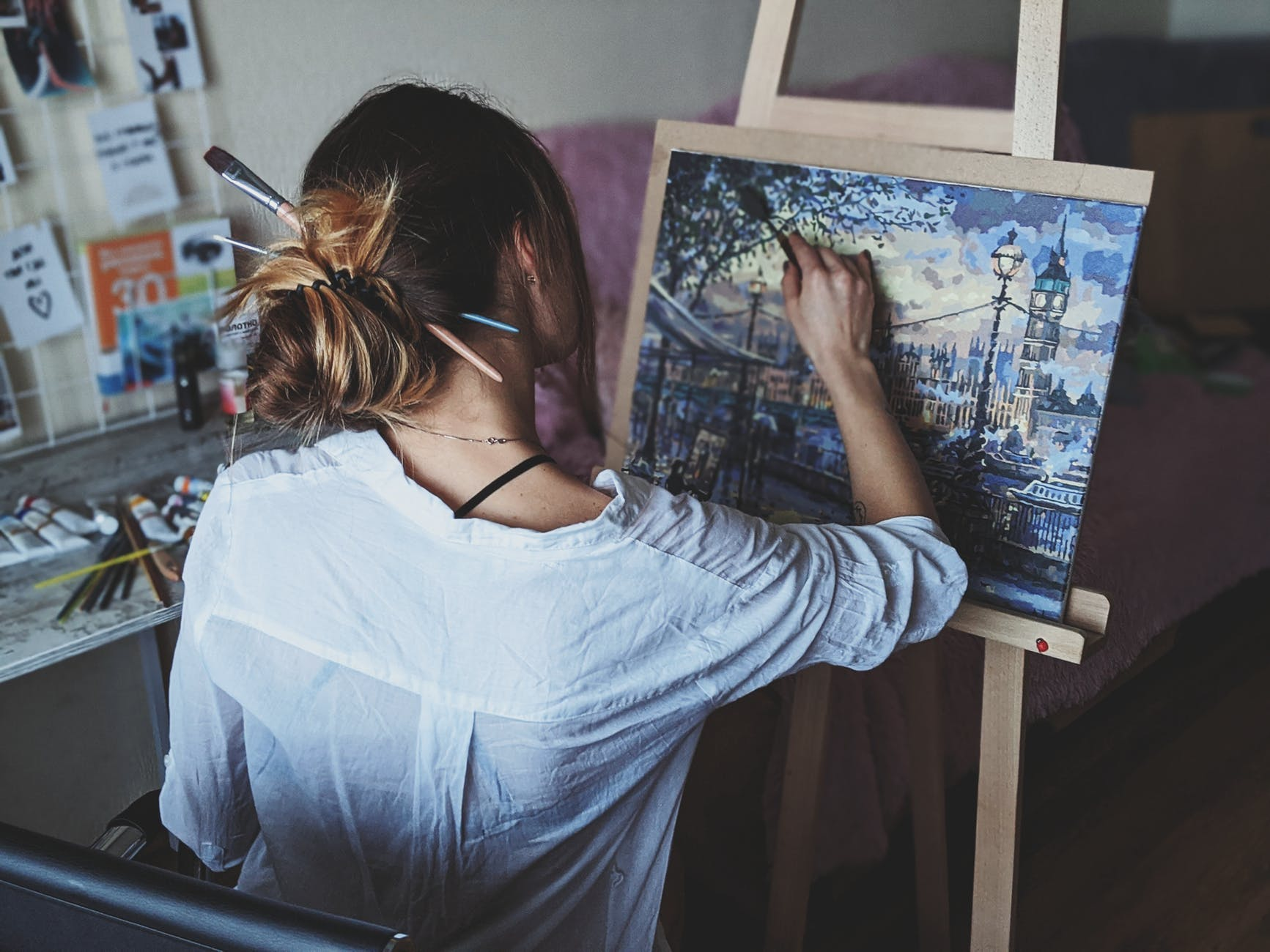 photo of woman in front of painting