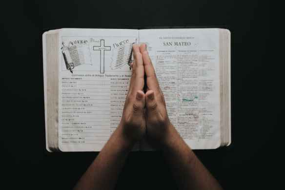 person placing hands on bible