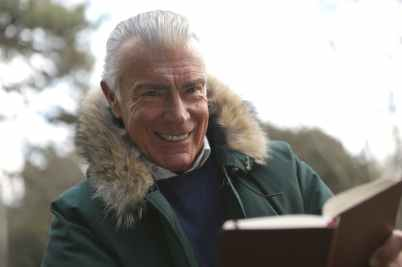 man in green winter jacket holding a brown book