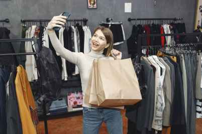 woman in white long sleeve shirt holding paper bags