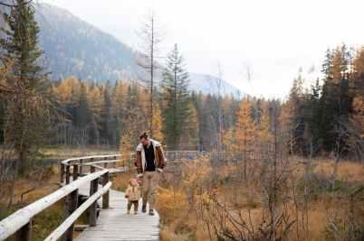 photo of man walking on wooden bridge