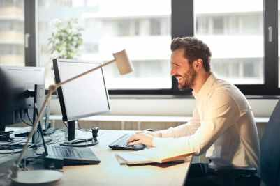 man in white dress shirt sitting on black rolling chair while facing black computer set and smiling