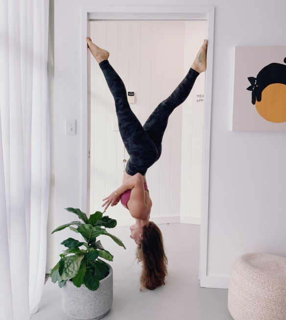woman in workout gear hanging upside down on doorway near green plants